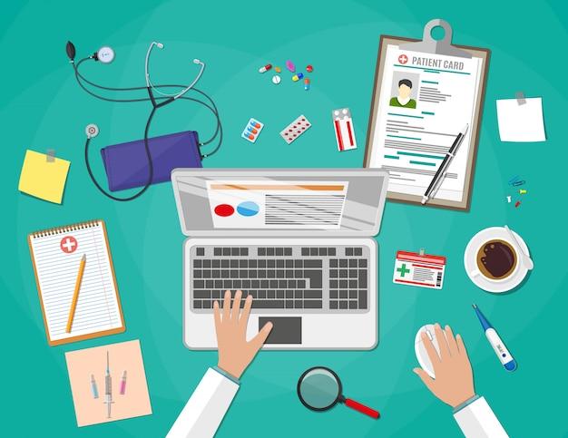 Mesa com laptop, dispositivos médicos e de saúde