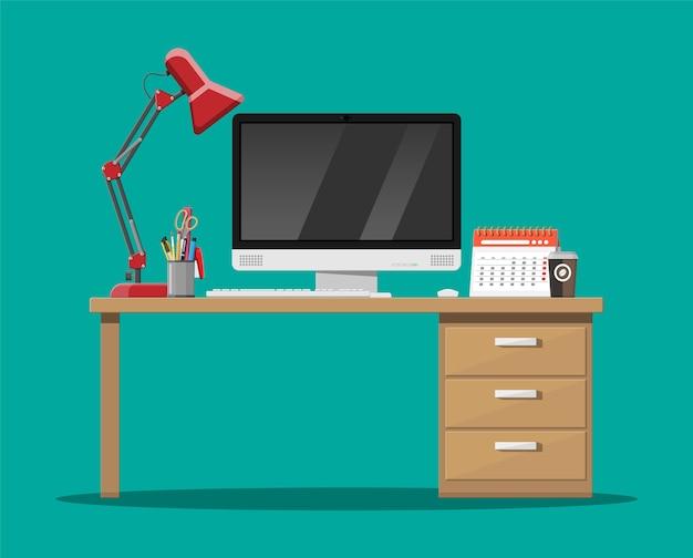Mesa de escritório com computador, abajur, xícara de café, calendário e porta-canetas.
