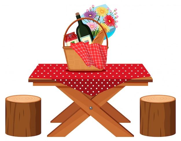 Mesa de piquenique com cesta de comida e bebida nela