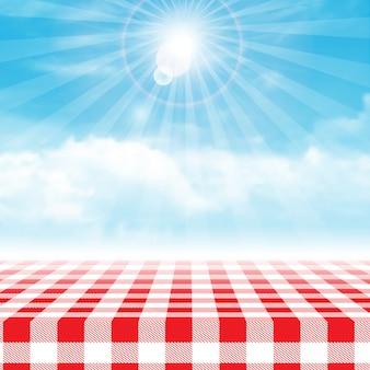 Mesa de piquenique de guingão contra o céu nublado azul