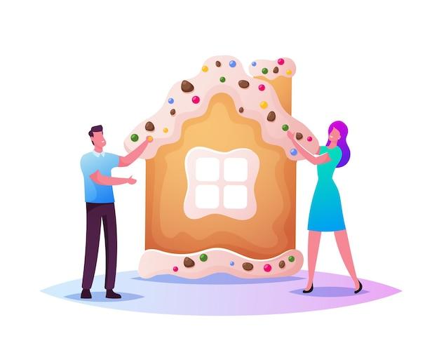 Minúsculos personagens masculinos e femininos fazendo uma enorme casa de pão de mel de natal e decorando com biscoitos e doces