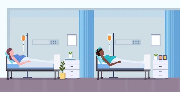 Misture as mulheres gravidas da raça com o conceito dos cuidados médicos da gravidez do conta-gotas que encontram-se na terapia intensiva