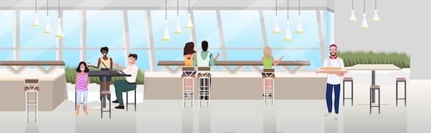 Misture as pessoas da corrida sentado a mesa de café, passar um tempo no restaurante pizzaria moderna interior plana horizontal banner comprimento total