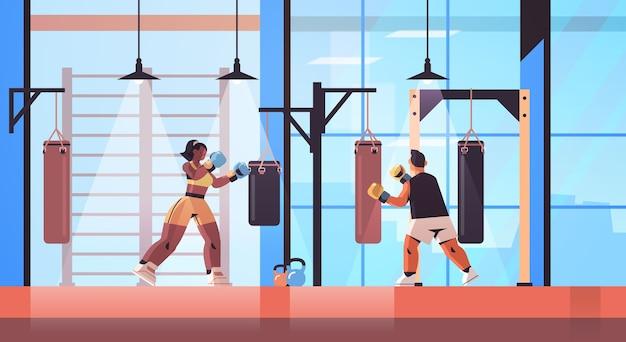 Misture boxeadores de corrida fazendo exercícios com treinamento de saco de pancadas estilo de vida saudável conceito de boxe interior moderno do clube da luta