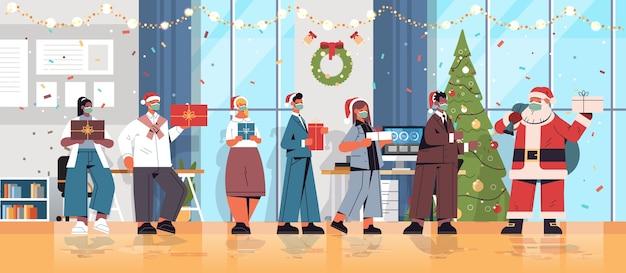 Misture colegas de corrida com o papai noel na máscara segurando presentes colegas de trabalho comemorando ano novo e feriados de natal escritório interior ilustração vetorial horizontal de corpo inteiro