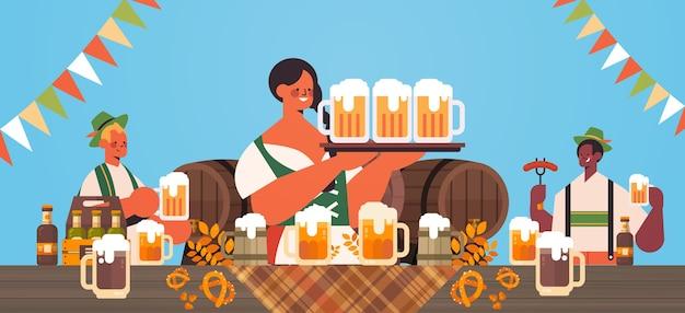Misture corrida garçons segurando canecas de cerveja conceito de celebração de festa oktoberfest pessoas em roupas tradicionais alemãs se divertindo