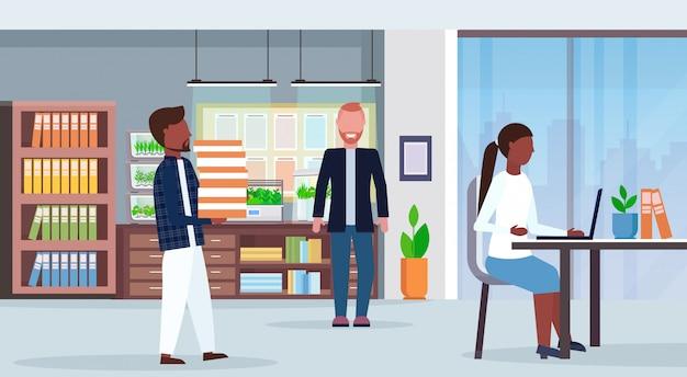 Misture os empresários reunidos no centro de trabalho criativo mesa mesa interior do escritório moderno com plantas de recipiente de vidro de terrário eletrônico crescendo conceito plana horizontal