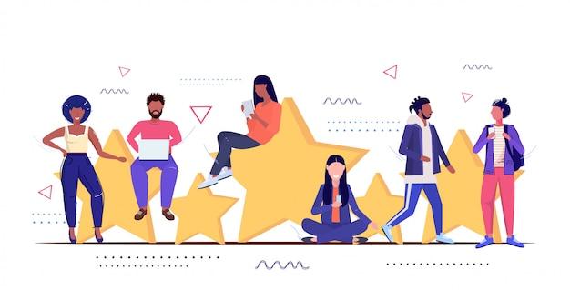 Misture pessoas de raça usando gadgets digitas os clientes revisam cinco estrelas avaliando o conceito de nível de satisfação de clientes, homens mulheres de pé juntos, esboço comprimento total