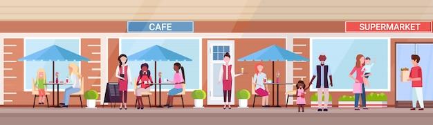 Misture raça pessoas visitantes sentado verão café loja clientes segurando compras na frente do supermercado exterior urbano rua conceito banner horizontal comprimento total
