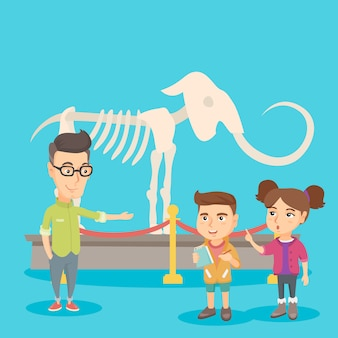 Miúdos com um professor que estuda um esqueleto no museu.