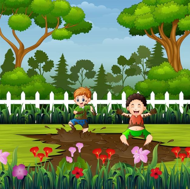 Miúdos felizes que jogam uma poça de lama no parque
