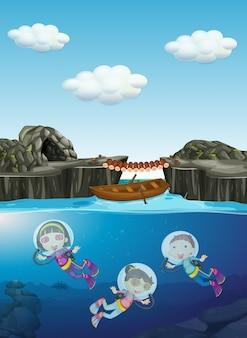 Miúdos que mergulham sob a água