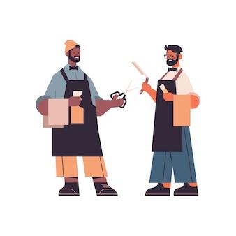 Mix raça barbeiros profissionais masculinos em uniforme em pé juntos na moda corte de cabelo conceito de barbearia descolados com tesouras e navalha em ilustração em vetor comprimento total