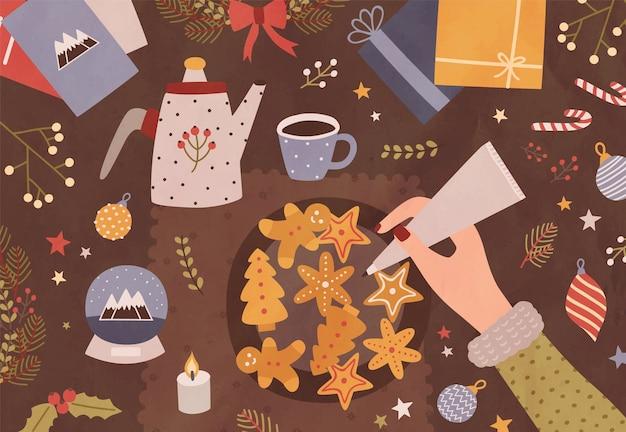 Modelo de cartão de natal com a mão segurando um saco de confeitar e decorando biscoitos