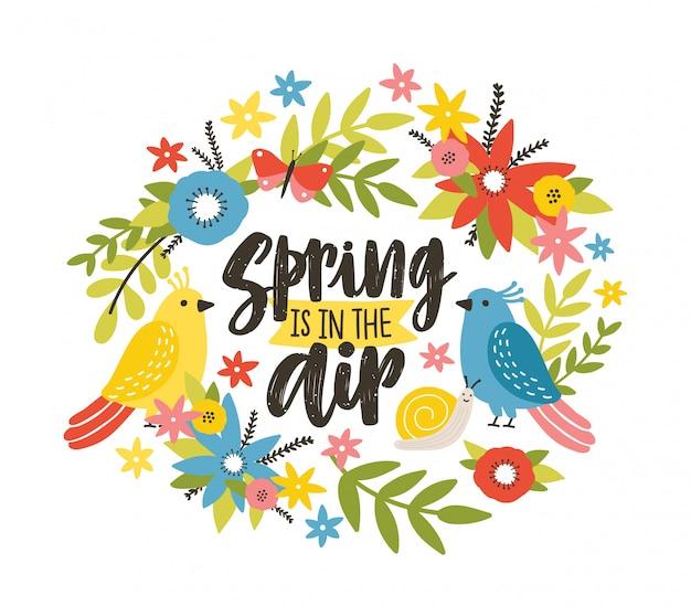 Modelo de cartão postal sazonal com a frase primavera está no ar escrita com fonte caligráfica cursiva, flores desabrochando prado selvagem, caracol, pássaros e borboletas. ilustração plana colorida.