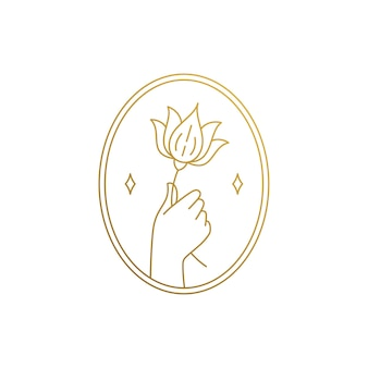 Modelo de design de emblema de estilo mínimo linear de mão segurando uma flor de lírio perto de estrelas em moldura dourada oval