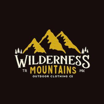 Modelo de logotipo vintage de roupas ao ar livre montanhas selvagens com textura gasto em fundo escuro