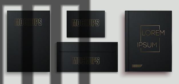 Modelo de marca comercial de papelaria preto, sobre fundo cinza. livro em branco, envelope, cartão de visita