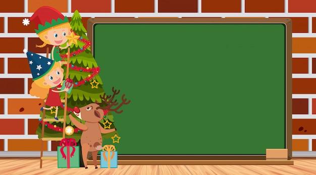 Moldura com meninas decorando a árvore de natal