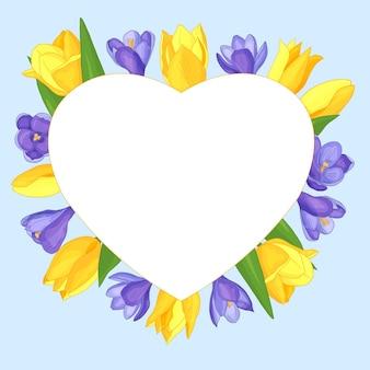 Moldura de coração com flores - tulipas amarelas e açafrões roxos em um fundo azul, dia dos namorados