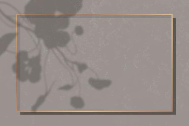 Moldura retangular dourada sobre fundo de mármore marrom sombreado por folhas