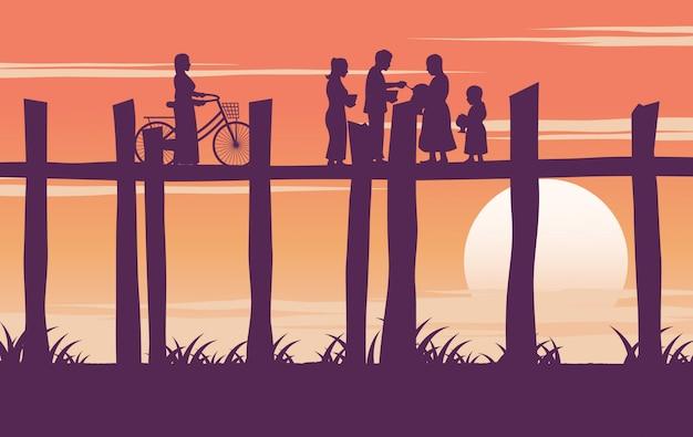 Monge pede comida e mulher segura bicicleta na ponte de madeira