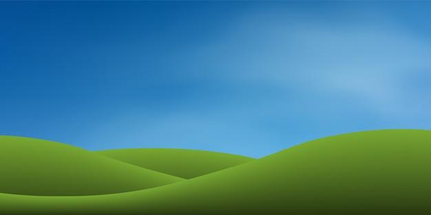 Monte da grama verde com céu azul.