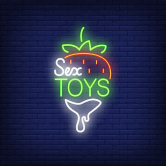 Morango com letras de brinquedos do sexo. sinal de néon no fundo do tijolo.