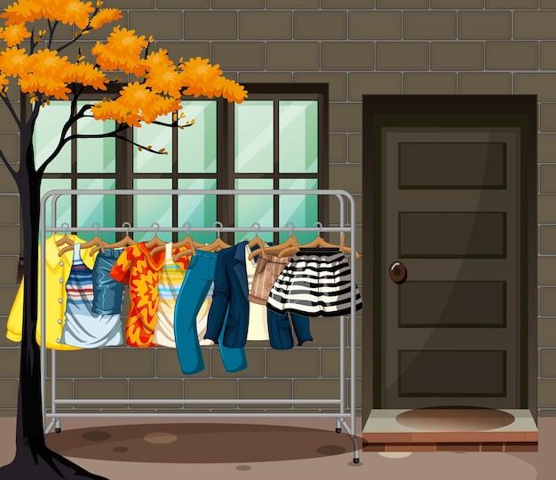 Muitas roupas penduradas em um cabideiro na frente da cena da casa