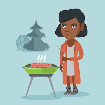Mulher africana cozinhar bife no churrasco.