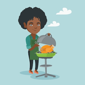 Mulher africana cozinhar frango no churrasco.