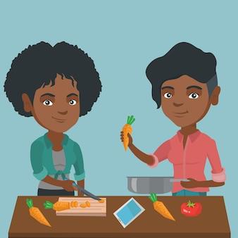 Mulher africana que cozinha a refeição vegetal saudável.