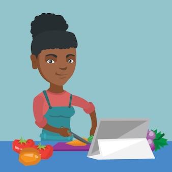 Mulher africana que cozinha a salada vegetal saudável.