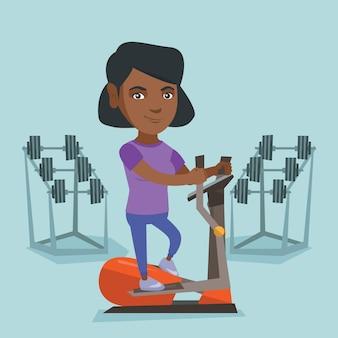 Mulher africana que exercita no instrutor elíptico.