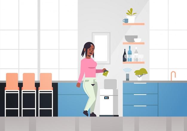 Mulher afro-americana colocando lixo na lixeira eletrônica