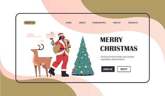 Mulher afro-americana com fantasia de papai noel segurando uma caixa de presente em pé com uma rena, ano novo, feliz natal, feriado, conceito, celebração, comprimento total, cópia horizontal, espaço, vetorial