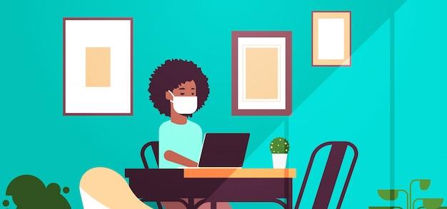 Mulher afro-americana na máscara protetora usando o laptop conceito de quarentena pandemia de coronavírus trabalho em casa educação freelance moderna sala interior retrato horizontal