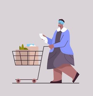 Mulher afro-americana sênior com carrinho de carrinho cheio de produtos, verificando a lista de compras em ilustração vetorial de comprimento total de supermercado