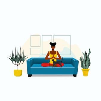 Mulher afro-americana sentada em posição de lótus, de pernas cruzadas, meditando no sofá da sala de estar