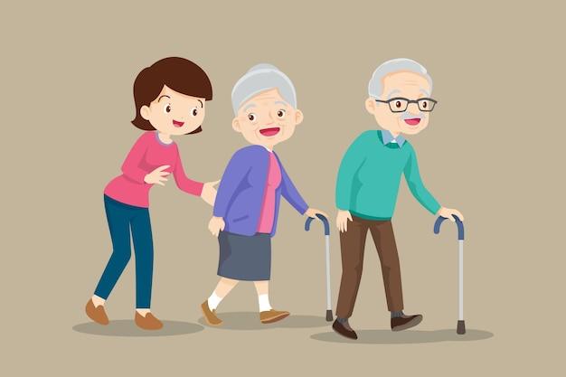 Mulher ajuda casal de idosos caminhando pela cana.