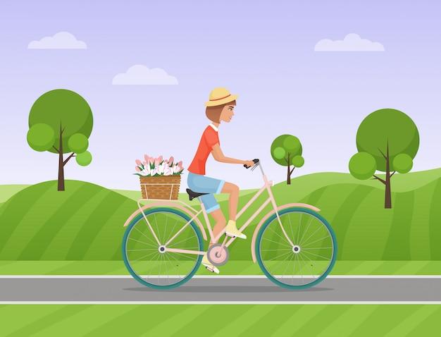 Mulher alegre, andar de bicicleta em uma estrada do parque