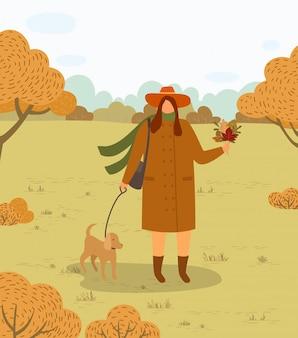 Mulher andando com cachorro na coleira no outono forest park