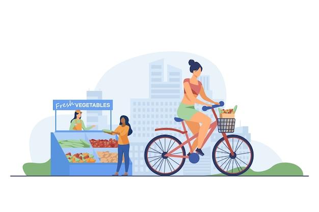 Mulher andando de bicicleta e comprando legumes frescos.