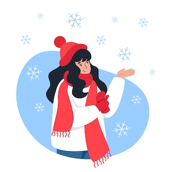 Mulher apanha flocos de neve com a mão, caminhada de inverno, clima de natal