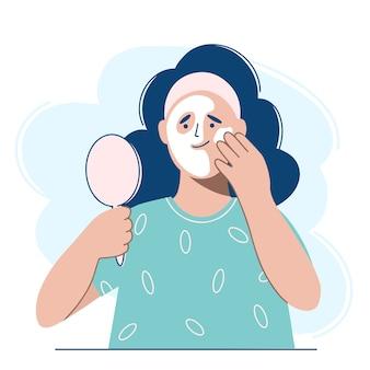 Mulher aplicando máscara cosmética no rosto.