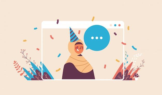 Mulher árabe com chapéu festivo com bolha de bate-papo comemorando festa de aniversário online auto-isolamento quarentena