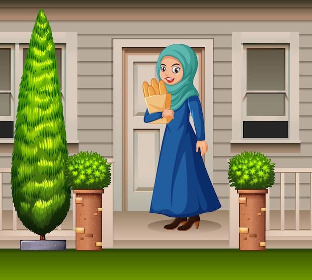 Mulher árabe na frente da casa