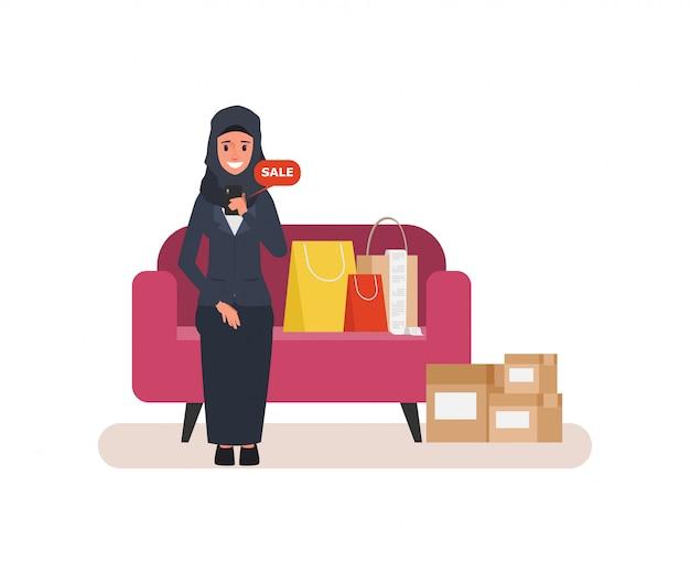Mulher árabe que compra em linha com telefone celular em casa.