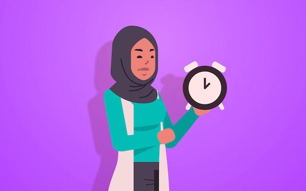 Mulher árabe segurando o conceito de prazo de gerenciamento de tempo relógio mulher de negócios árabe com despertador retrato de personagem de desenho animado feminino horizontal
