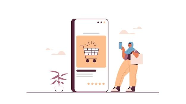 Mulher árabe usando smartphone comprando coisas em loja online consumismo compras online comércio eletrônico compra inteligente